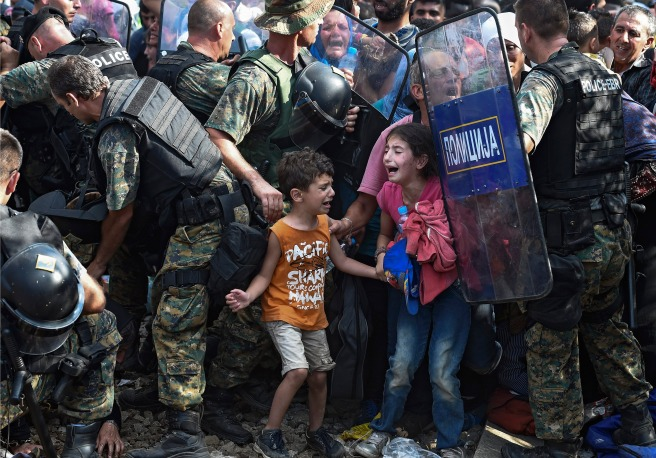 Children cry as migrants waiting on the Greek side of the border break through a cordon of Macedonian special police forces to cross into Macedonia, near the southern city of Gevgelija, The Former Yugoslav Republic of Macedonia, 21 August 2015. Macedonian police clashed with thousands of migrants attempting to break into the country after being stranded in no-man's land overnight, marking an escalation of the European refugee crisis for the Balkan country.  EPA/GEORGI LICOVSKI